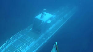 a close up of a swimming pool: Submarine passes beneath Scuba divers