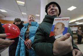 A woman shows a passport cover with an image of Russian President Vladimir Putin as she visits a polling station during the presidential election in Moscow, Russia March 18, 2018.