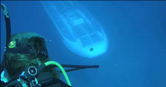 Spooky moment when a submarine passes beneath scuba divers