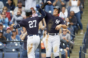 New York Yankees ' Giancarlo Stanton (27) victorious after hitting home run with Aaron Judge