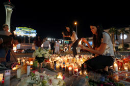 Elisabeth Apcar (C) and her cousin Dashenka Giraldo, both of Las Vegas, light candles at a makeshift memorial for shooting victims at the Las Vegas Strip and Sahara Avenue in Las Vegas, Nevada, October 4, 2017.