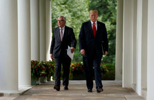 European Commission President Jean-Claude Juncker and U.S. President Donald Trump walk down the West Wing colonnade together as they arrive from the Oval Office to speak to the news media in the Rose Garden of the White House in Washington, U.S., July 25, 2018. REUTERS/Joshua Roberts