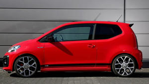 a red car parked in front of a building: VW Up! GTI by B&B Automobiltechnik
