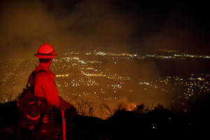 Firefighters watch for flare ups as they prevent the flames from the Holy Fire from crossing the Ortega Highway in Lake Elsinore, Calif., on Aug. 10, 2018.