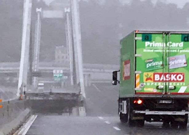 A green truck stops just before the spot that the A10 motorway collapsed