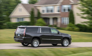 a car parked in front of a house: 2018 Cadillac Escalade ESV driving