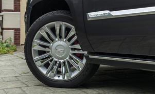 a car parked on the side of a building: 2018 Cadillac Escalade ESV wheel