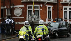 Police motorcyclists briefly stop outside the Ecuadorian embassy in London, Tuesday, Feb. 13, 2018