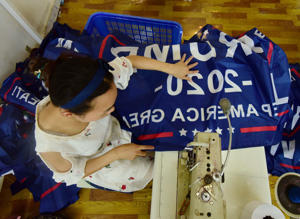 This photo taken on July 13, 2018 shows a Chinese employee sewing a banner declaring US President Donald Trump's re-election intentions that reads 'Trump 2020: Keep America Great' at a factory in Fuyang in China's eastern Anhui province. - As the Sino-US trade war rages, a factory set amid corn and mulberry fields in central China stitches together US and 'Trump 2020' flags -- and business is good. (Photo by - / AFP) / China OUT        (Photo credit should read -/AFP/Getty Images)