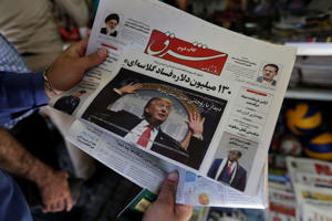 A man takes a glance at a newspaper with a picture of US president Donald Trump on the front page, in the capital Tehran on July 31, 2018. - Iran's currency traded at a fresh record-low of 119,000 to the dollar today, a loss of nearly two-thirds of its value since the start of the year as US sanctions loom. (Photo by ATTA KENARE / AFP)        (Photo credit should read ATTA KENARE/AFP/Getty Images)