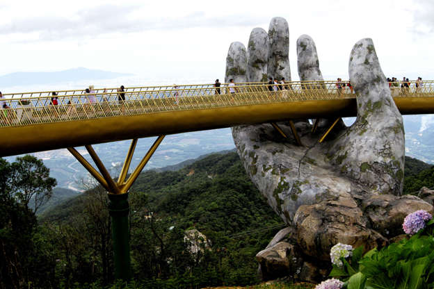In this photograph taken on July 31, 2018, visitors walk along the 150-meter long Cau Vang 'Golden Bridge' in the Ba Na Hills near Danang. - Nestled in the forested hills of central Vietnam two giant concrete hands emerge from the trees, holding up a glimmering golden bridge crowded with gleeful visitors taking selfies at the country's latest eccentric tourist draw. (Photo by Linh PHAM / AFP)        (Photo credit should read LINH PHAM/AFP/Getty Images)
