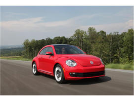 a red car parked on the side of a road: 2018 Volkswagen Beetle