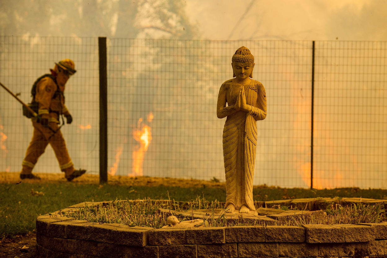 Slide 7 of 95: Flames lick behind a Buddha lawn statue as the Ranch Fire tears down New Long Valley Rd near Clearlake Oaks, California, on Saturday, August 4, 2018. - The Ranch Fire is part of the Mendocino Complex, which is made up of two blazes, the River Fire and the Ranch Fire. (Photo by NOAH BERGER / AFP)        (Photo credit should read NOAH BERGER/AFP/Getty Images)