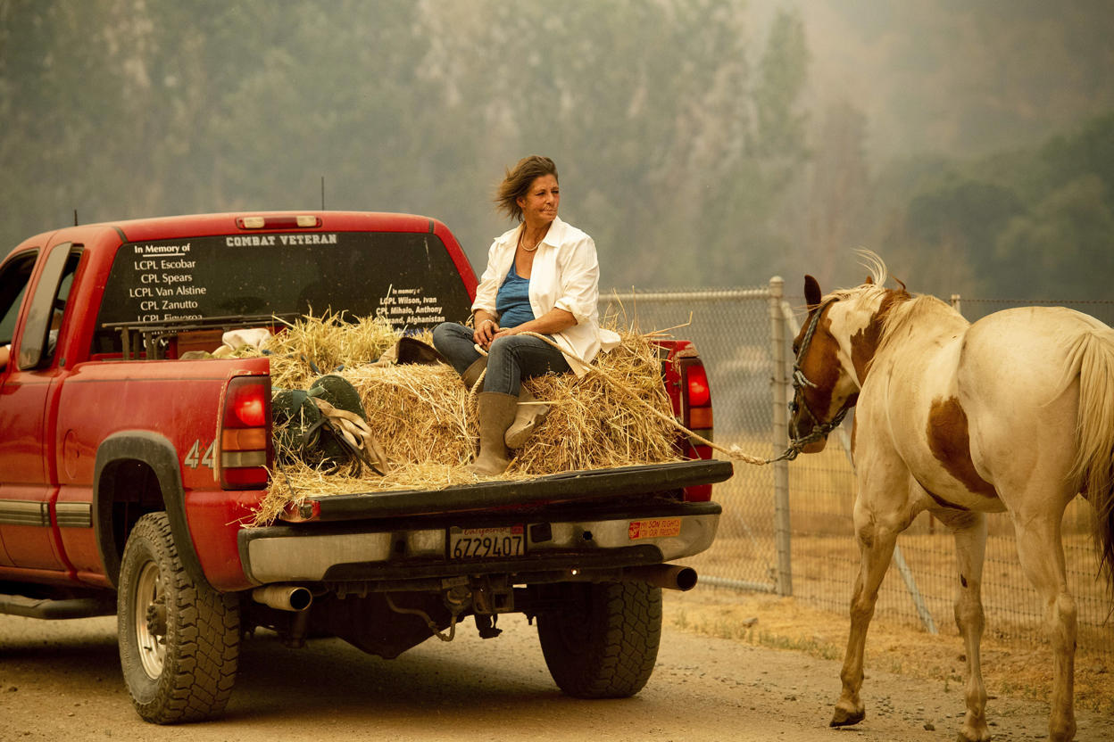 Slide 9 of 95: Debbie Prior evacuates a horse as the Ranch Fire tears down New Long Valley Rd near Clearlake Oaks, California, on Saturday, August 4, 2018. - The Ranch Fire is part of the Mendocino Complex, which is made up of two blazes, the River Fire and the Ranch Fire. (Photo by NOAH BERGER / AFP)        (Photo credit should read NOAH BERGER/AFP/Getty Images)