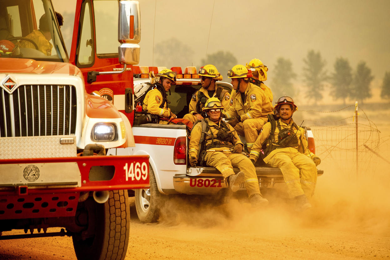 Slide 6 of 95: Firefighters ride in the back of a pickup truck while battling the Ranch Fire on New Long Valley Rd near Clearlake Oaks, California, on Saturday, August 4, 2018. - The Ranch Fire is part of the Mendocino Complex, which is made up of two blazes, the River Fire and the Ranch Fire. (Photo by NOAH BERGER / AFP)        (Photo credit should read NOAH BERGER/AFP/Getty Images)