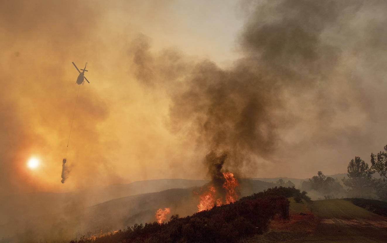 Slide 5 of 95: A helicopter drops water on a burning hillside during the Ranch Fire in Clearlake Oaks, Calif., Sunday, Aug. 5, 2018.
