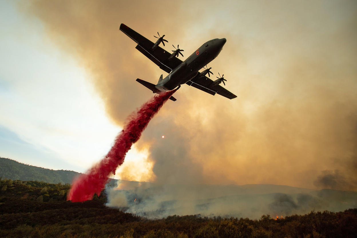 Slide 4 of 95: An air tanker drops retardant on the Ranch Fire, part of the Mendocino Complex Fire, burning along High Valley Rd near Clearlake Oaks, California, on August 5, 2018. - Several thousand people have been evacuated as various fires swept across the state, although some have been given permission in recent days to return to their homes.
