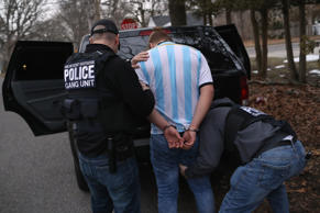 Homeland Security Investigations (HSI) ICE agents frisk a suspected MS-13 gang member and Honduran immigrant after arresting him at his home on March 29, 2018 in Brentwood, New York.