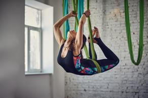 Young woman making antigravity fly yoga exercises in a loft interior