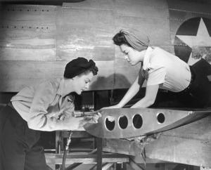 Female workers working on plane in the 1940s .