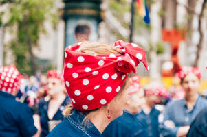 San Francisco, CA, USA - June 25, 2017: The 2017 Pride Parade the profile of a woman dressed like 'Rosie the Riveter' in sharp focus along with accompanying 'Rosie the Riveter' costumes in the background.