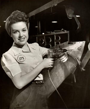 Woman working on aircraft assembly line.