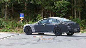 a close up of a car going down the street: New Genesis G80 spy photo