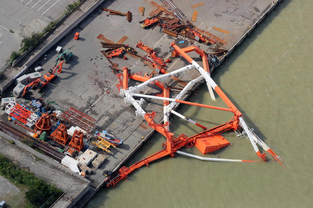 Slide 1 of 29: An aerial view from a Jiji Press helicopter shows a crane that toppled due to strong winds in Nishinomiya city, Hyogo prefecture on September 5, 2018, after typhoon Jebi hit the west coast of Japan. - The toll in the most powerful typhoon to hit Japan in a quarter century rose on September 5 to nine, with thousands stranded at a major airport because of storm damage. (Photo by JIJI PRESS / JIJI PRESS / AFP) / Japan OUT        (Photo credit should read JIJI PRESS/AFP/Getty Images)