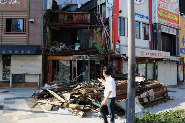 Slide 4 of 29: A man walks past a wooden house destroyed by strong winds from typhoon Jebi in Osaka on September 5, 2018. - Typhoon Jebi left a trail of destruction across the country, killing 11 people and injuring hundreds more as it battered western Japan with ferocious winds and lashing rain. (Photo by JIJI PRESS / JIJI PRESS / AFP) / Japan OUT        (Photo credit should read JIJI PRESS/AFP/Getty Images)