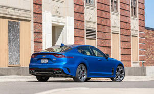 a blue car parked in front of a building: The Kia Stinger GT Continues to Grow on Us