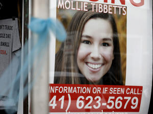 A poster for missing University of Iowa student Mollie Tibbetts hangs in the window of a local business, Tuesday, Aug. 21, 2018, in Brooklyn, Iowa.