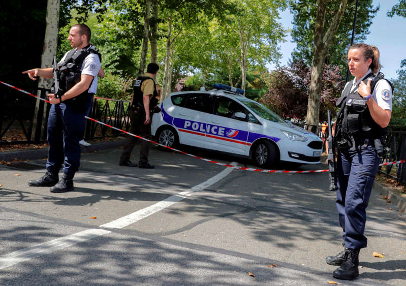 French police officials stand alert as they cordon off a road in Trappes, south-west of Paris on August 23, 2018, following a knife attack. - A man armed with a knife killed his mother and sister and seriously injured another person in a town near Paris, officials said. The man, who police said had been on a terror watch list since 2016, was later shot and killed after confronting police in Trappes. The motive for the violence remains unclear, but the Islamic State group claimed the attack via its propaganda channel. (Photo by Thomas SAMSON / AFP)        (Photo credit should read THOMAS SAMSON/AFP/Getty Images)