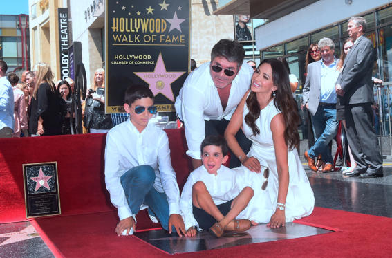Slide 1 of 25: Television Producer Simon Cowell poses with his family on his Hollywood Walk of Fame Star at a ceremony in Hollywood, California, on August 22, 2018. (Photo by Frederic J. BROWN / AFP)        (Photo credit should read FREDERIC J. BROWN/AFP/Getty Images)