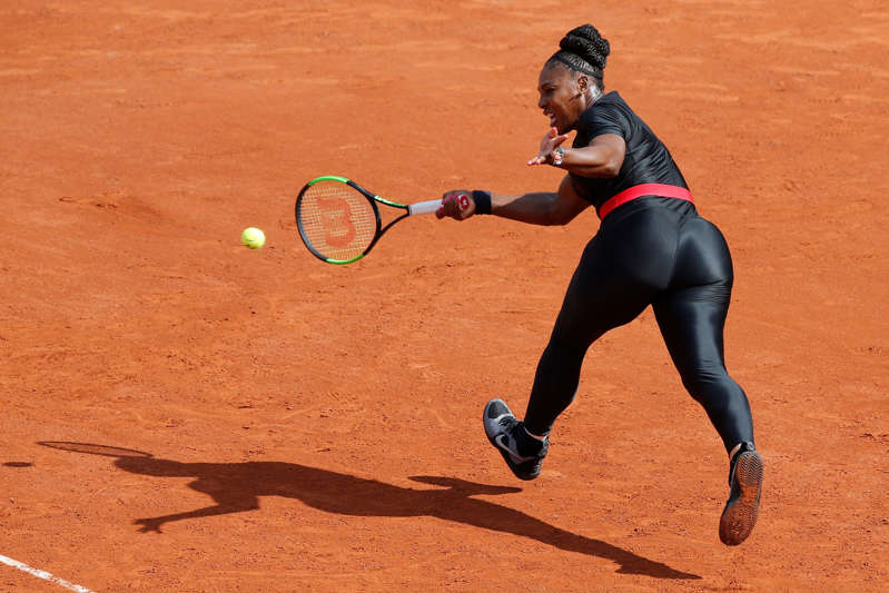 """FILE - In this May 29, 2018 file photo, Serena Williams of the U.S. returns a shot against Krystyna Pliskova of the Czech Republic during their first round match of the French Open tennis tournament at the Roland Garros stadium in Paris. Serena Williams will no longer be allowed to wear her sleek, figure-hugging catsuit at the French Open. The French Tennis Federation president, Bernard Giudicelli, says the tournament that Williams has won three times is introducing a dress code to regulate players' uniforms because """"I think that sometimes, we've gone too far."""" (AP Photo/Michel Euler, File)"""
