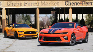 a car parked in front of a building: Chevy Camaro SS Vs. Ford Mustang GT: Top Down Tussle