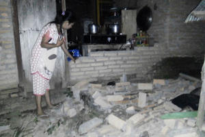 A resident is seen beside the collapsed brick wall of her house at Tobadak village in Central Mamuju, western Sulawesi province, on September 28, 2018, after a strong earthquake hit the area. - Indonesia was rocked by a powerful 7.5 magnitude earthquake on September 28, just hours after at least one person was killed by a collapsing building in the same part of the country. (Photo by NURPADILA / AFP)        (Photo credit should read NURPADILA/AFP/Getty Images)
