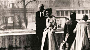 a man and a woman standing in front of a building