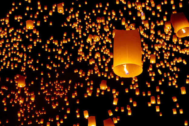 Slide 14 de 24: Picture of numerous hot air lanterns in sky floating away at Yee Peng or Yi Peng Festival in Chiang Mai Province in Chiang Mai, Thailand.The picture details one fire lantern closeup and several in background.