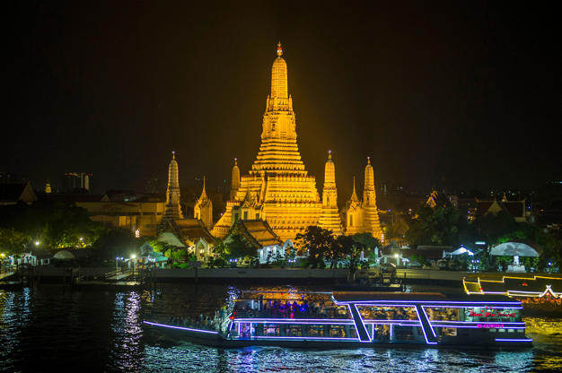 Slide 8 de 24: A tourist boat passes the glowing Wat Arun, a major Buddhist temple and landmark on March 24, 2018 as many landmarks in Thailand participate in the global Earth Hour campaign. (Photo by Romeo GACAD / AFP)        (Photo credit should read ROMEO GACAD/AFP/Getty Images)