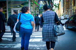 Two obese women crossing Lexington Avenue carrying bags and talking as they cross.