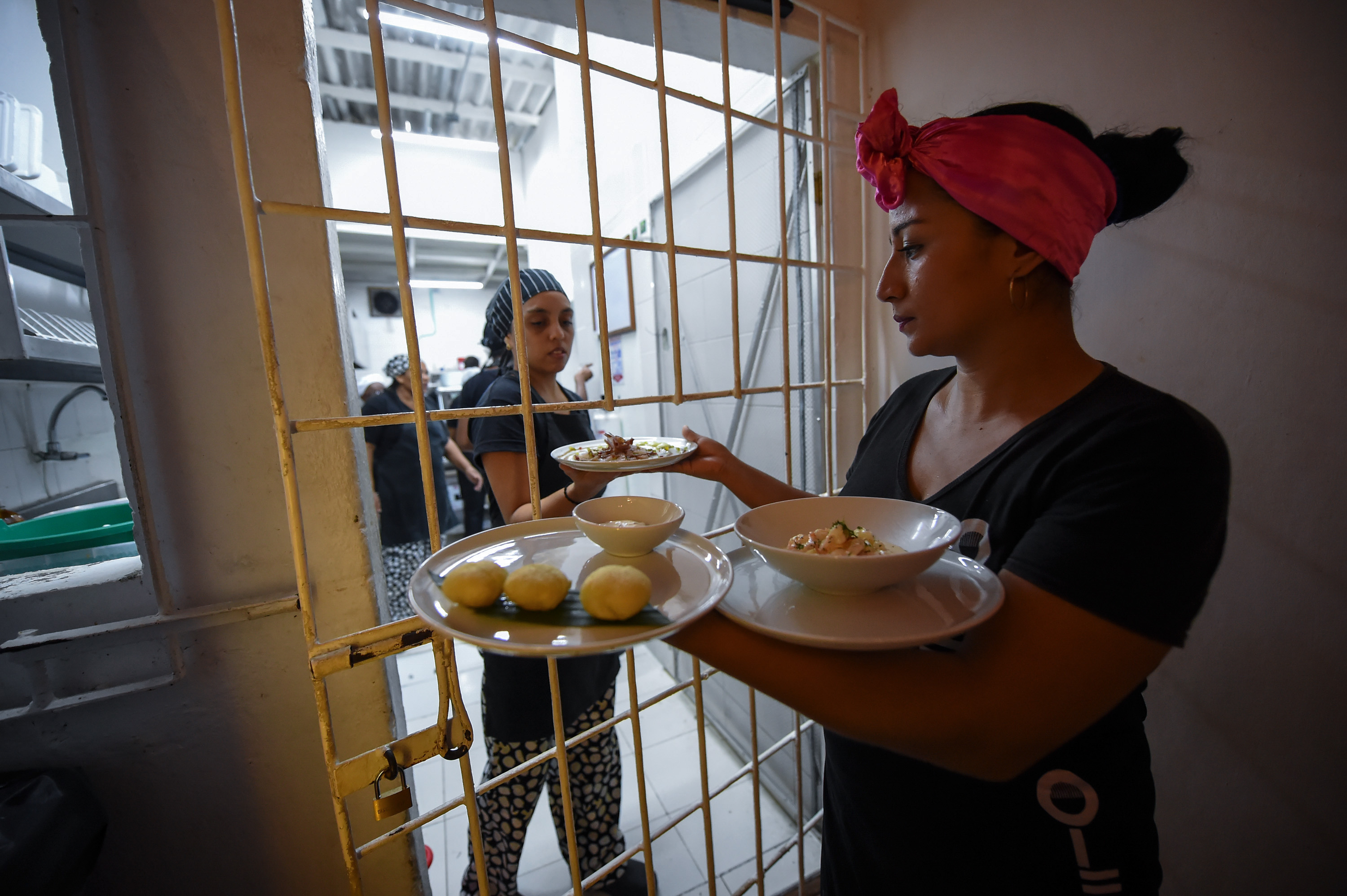 Slide 65 of 77: Colombian inmates work at the Interno restaurant in the San Diego jail in Cartagena, Colombia on August 24, 2017.  The Interno is the first restaurant in the country to operate inside a women's prison, sponsored by the Internal Theater foundation. Inmates receive training in this initiative that gives them a second chance at life and reintegration in society. / AFP PHOTO / Raul Arboleda        (Photo credit should read RAUL ARBOLEDA/AFP/Getty Images)