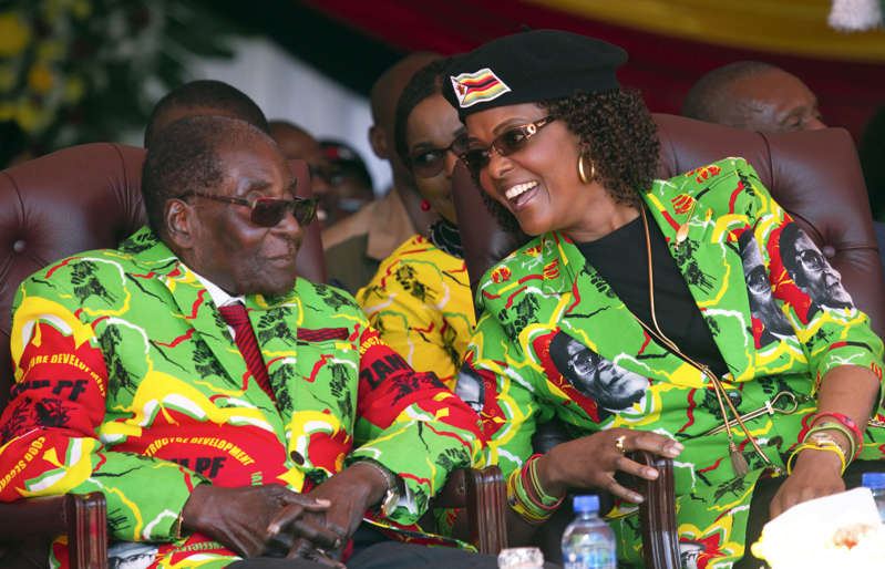 FILE -- In this Friday June, 2, 2017 file photo, Zimbabwe's President Robert Mugabe, left, and his wife Grace attend a youth rally in Marondera, Zimbabwe. Zimbabwe's presidential spokesman says that former president Robert Mugabe and his wife Grace have traveled to Singapore. Zimbabwe's presidential spokesman said Tuesday, Dec. 12, 2017, that former president Robert Mugabe and his wife Grace have traveled to Singapore on their first international trip since he resigned last month.  (AP Photo/Tsvangirayi Mukwazhi, File)