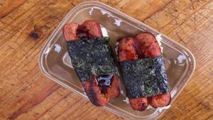 a plate of food with a fork and knife: Richard Blais' Hot Dog Musubi