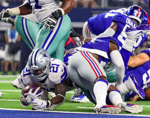 ARLINGTON, TX - SEPTEMBER 16: Ezekiel Elliott #21 of the Dallas Cowboys scores a touchdown against the New York Giants in the fourth quarter of a football game at AT&T Stadium on September 16, 2018 in Arlington, Texas.