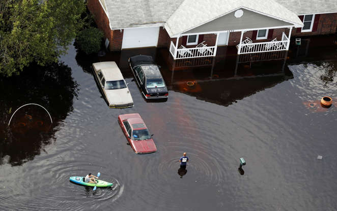 Slide 2 of 80: A man paddles a kayak in a flooded neighborhood in the aftermath of Hurricane Florence, in Fayetteville, N.C., Monday, Sept. 17, 2018. (AP Photo/Gerald Herbert)