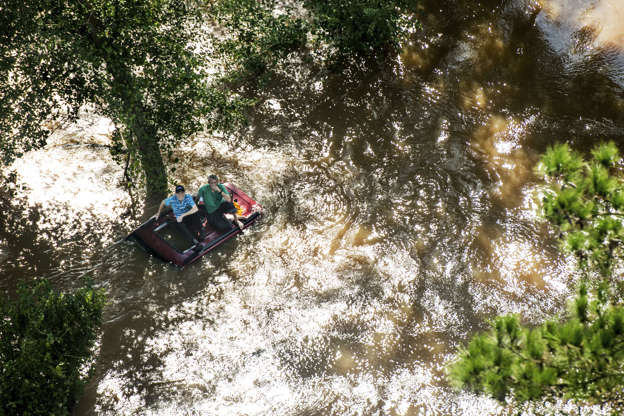 第1页,共80页:佛罗伦萨飓风袭击了卡罗来纳州,于2018年9月17日在南卡罗来纳州华莱士附近(AP Photo / Sean Rayford),两人坐在洪水中的车顶上