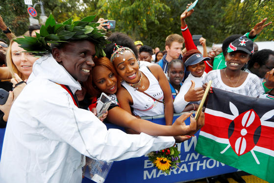 Slide 1 of 88: Kenya's Eliud Kipchoge takes selfies with fans after winning the Berlin Marathon and breaking the World Record