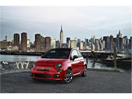 a red car parked next to a body of water: 2018 FIAT 500