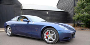 a car parked in front of a house: The auction of Slowhand's grand tourer is an under-the-radar opportunity to own a V-12 prancing horse at a reasonable (for Ferrari) price.