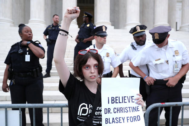Slide 3 of 72: A demonstrator protests in front of police after they cleared the steps of the U.S. Supreme Court building while Judge Brett Kavanaugh was being sworn in as an Associate Justice of the court inside on Capitol Hill in Washington, U.S., October 6, 2018.  REUTERS/Jonathan Ernst